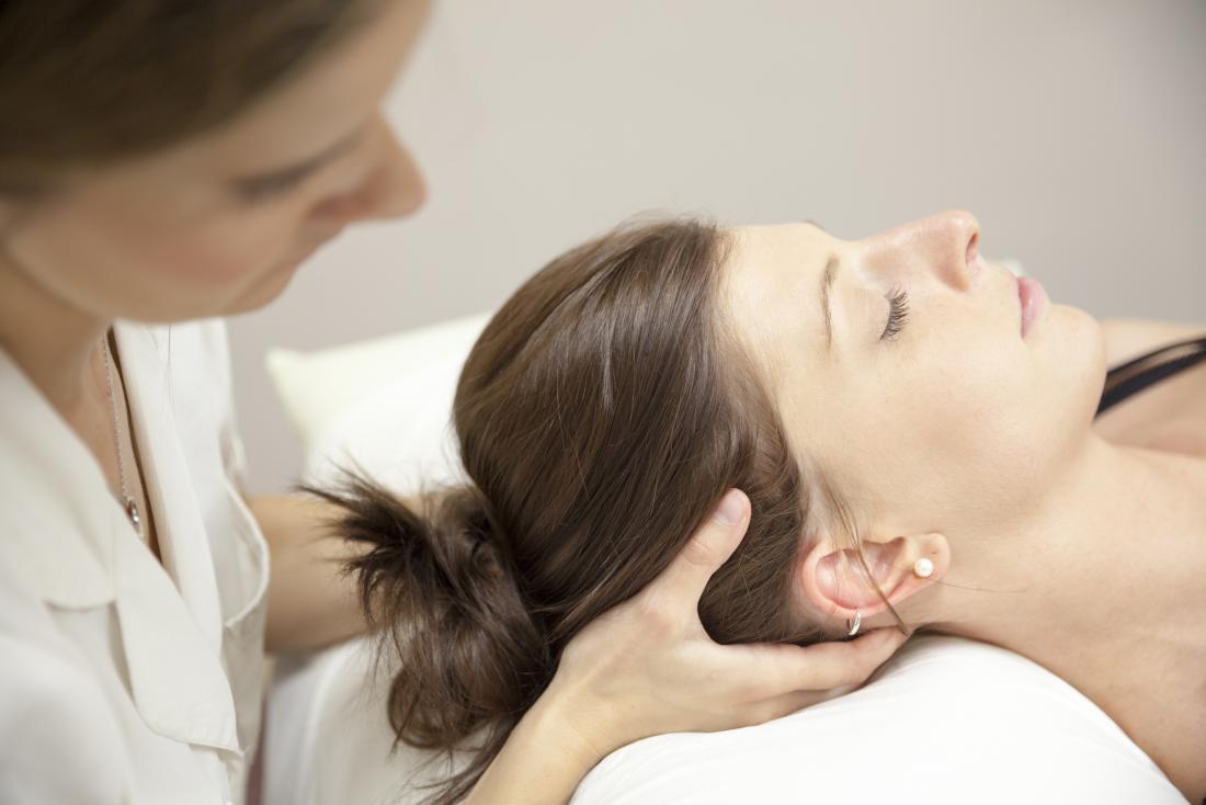 Quiroprático que ajusta a cabeça e o pescoço do paciente na cama.