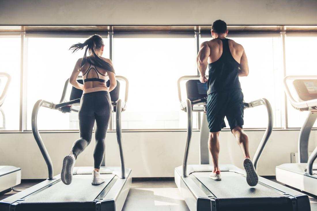 Homme et femme l'un à côté de l'autre sur des machines de course dans la salle de gym,