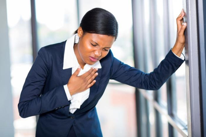 Uma mulher está sentindo dor no peito.