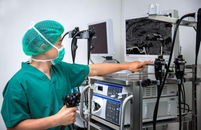Um médico olha para um monitor de endoscopia.