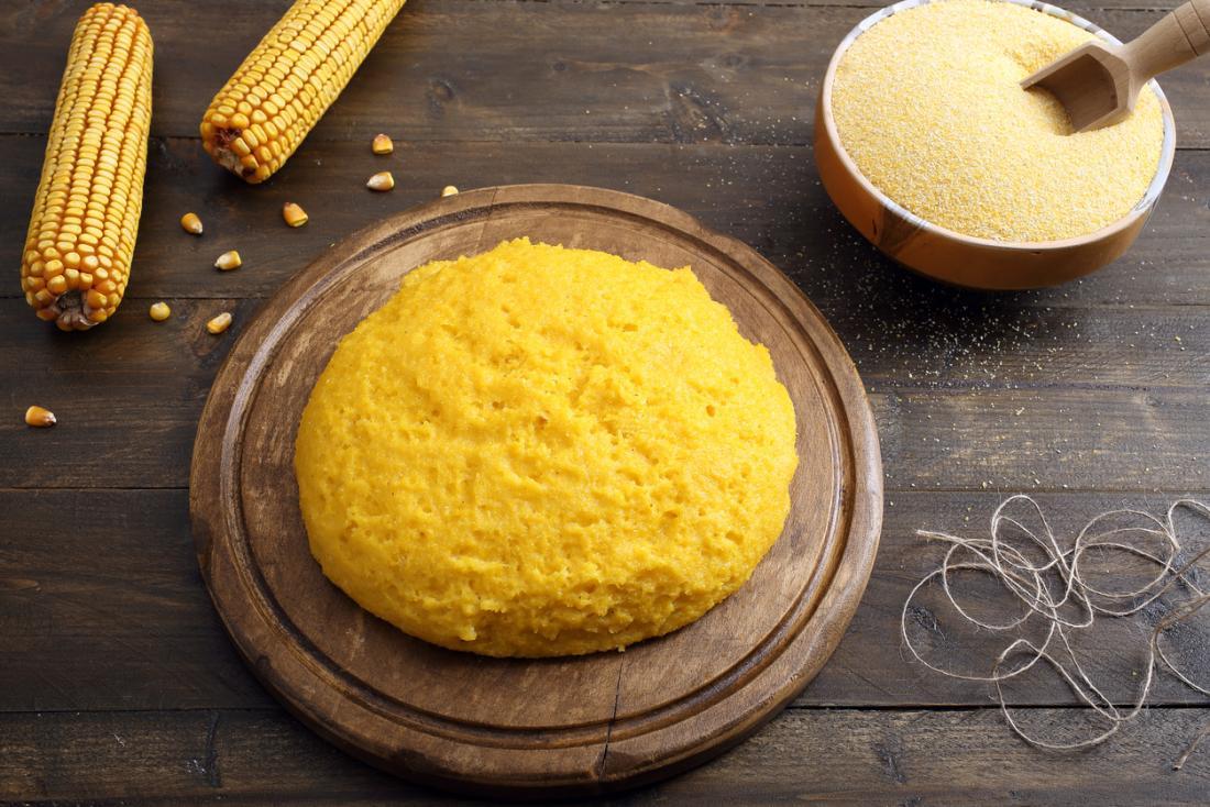 Polenta sur une planche à découper en bois, avec maïs doux et grain de maïs sur la table en bois.