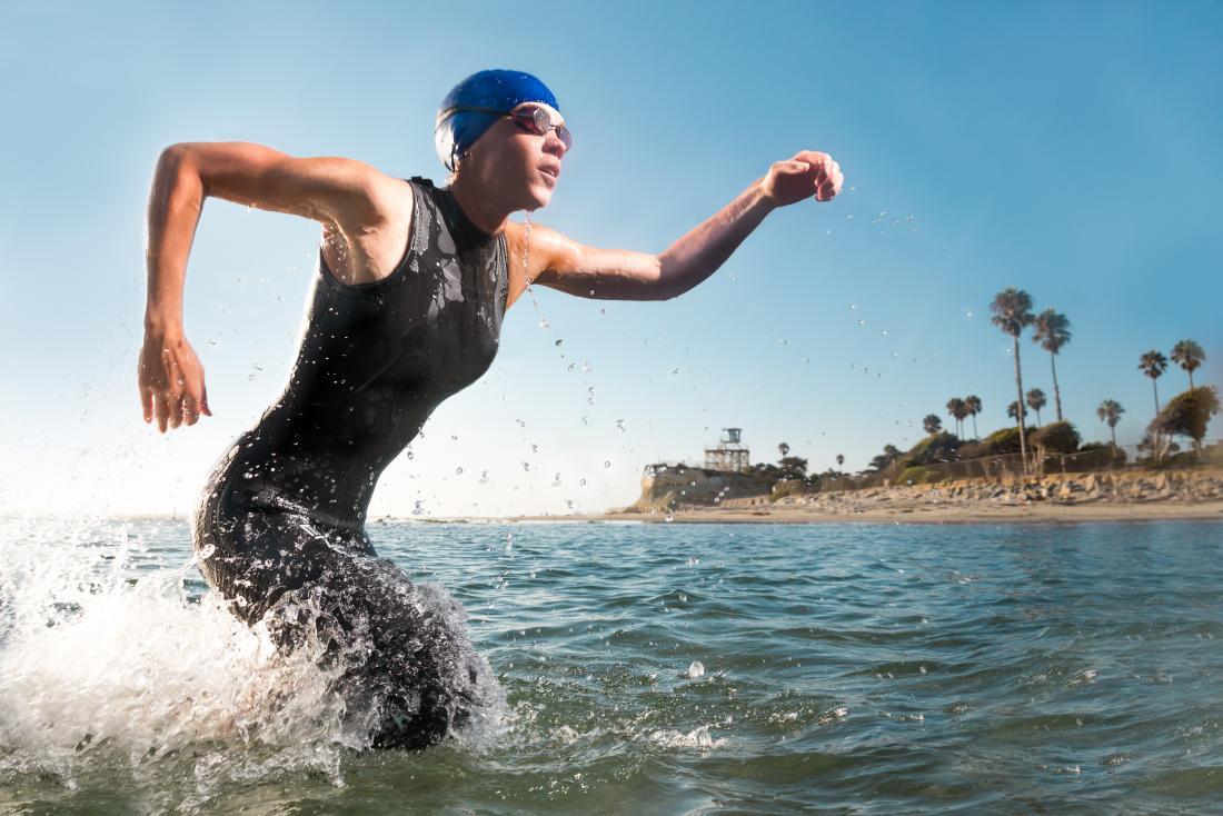 Muskulöser weiblicher Schwimmer, der in einem Triathlon, aus Meer hinausläuft konkurriert.