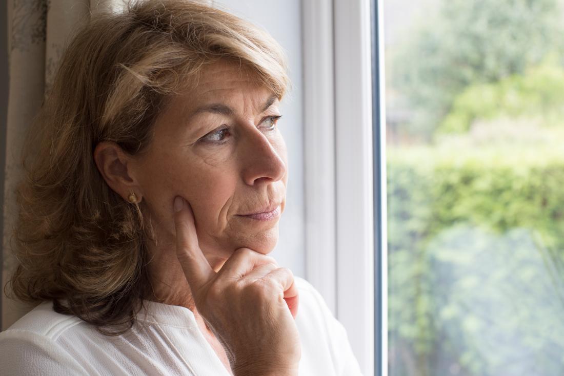 donna triste guardando fuori dalla finestra