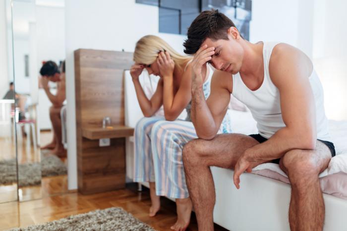Човек и жена изглеждат загрижени в спалнята
