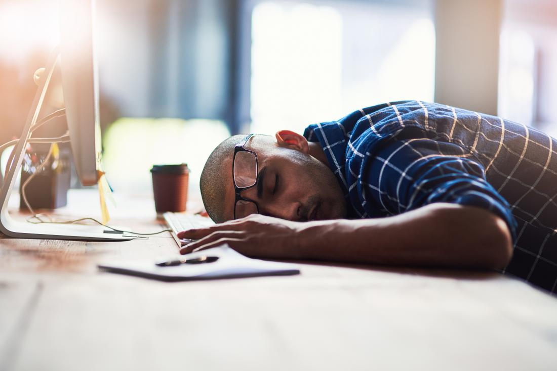 デスクで眠っている男性は、疲れてストレスから疲れています。