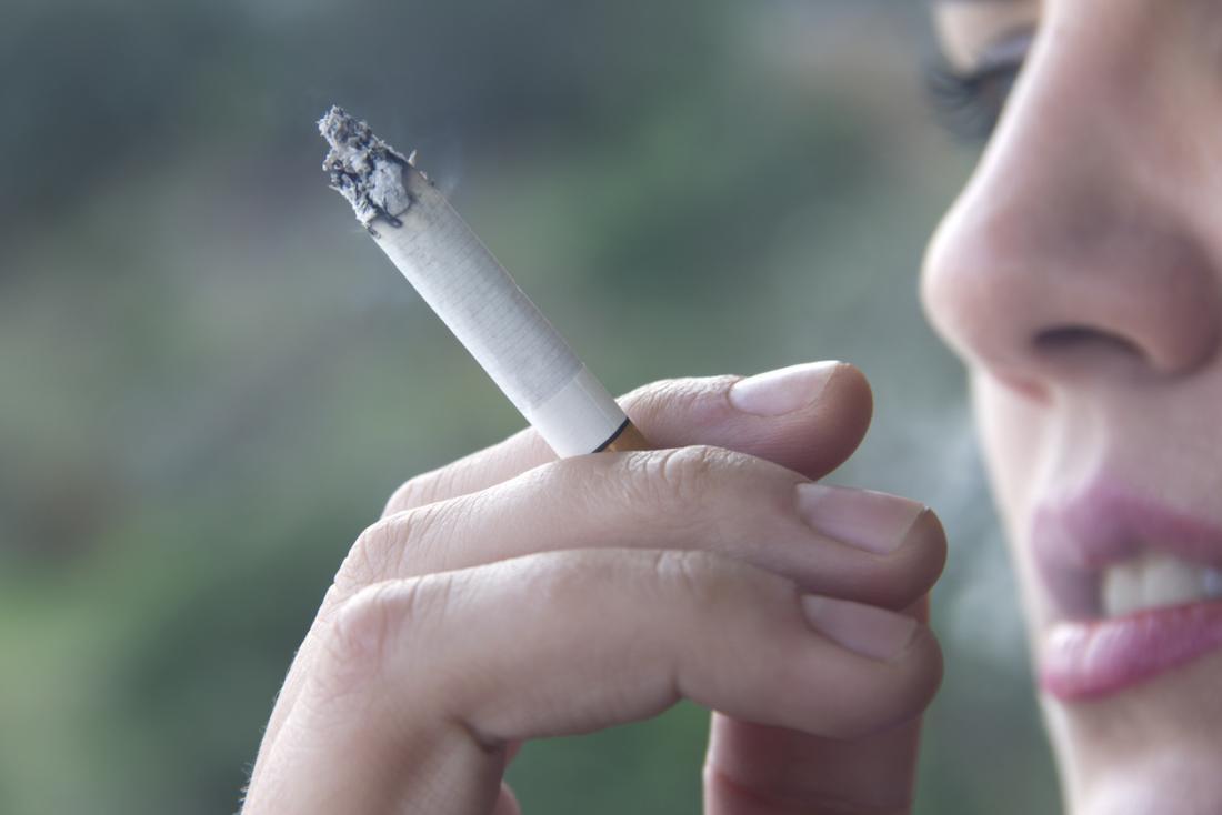 Feche acima da mulher que guarda um cigarro e que fuma.