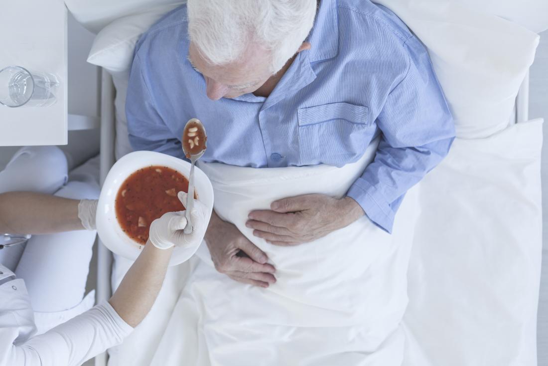 älterer Mann, der in einem Krankenhausbett gefüttert wird, kann verringerter Appetit ein Zeichen des Todes sein