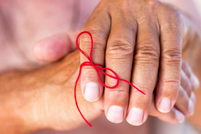 chaîne rouge sur un doigt à retenir