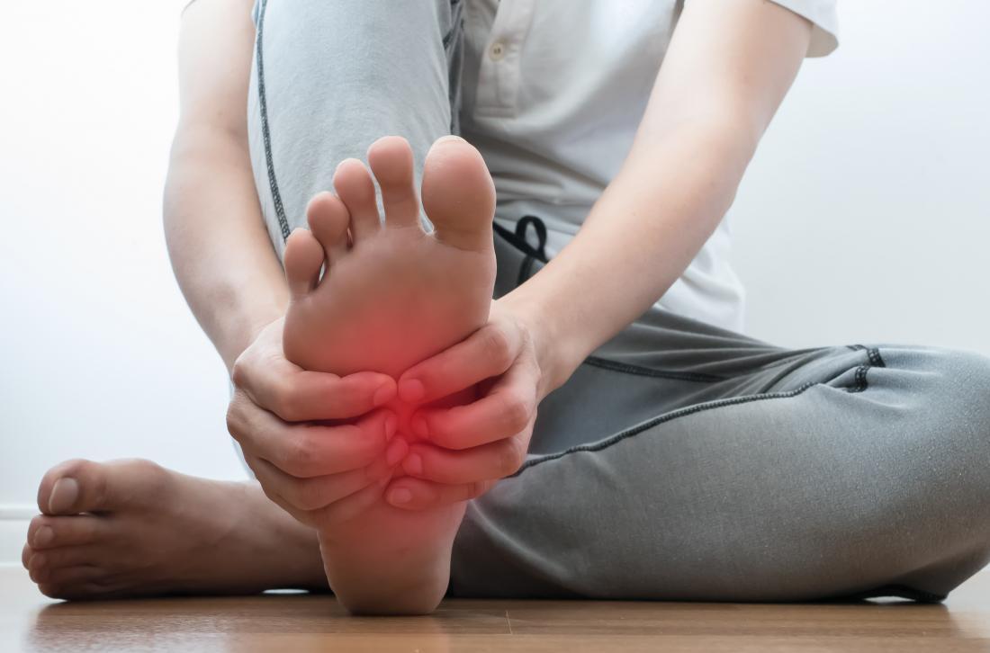 Homme tenant son pied avec des symptômes possibles du pied cassé