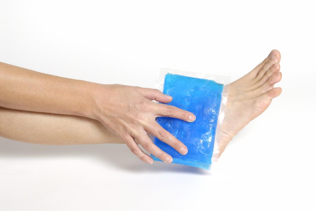Personne tenant un sac de glace sur son pied qui est recommandé en tant que premiers soins pour les symptômes de pied cassé