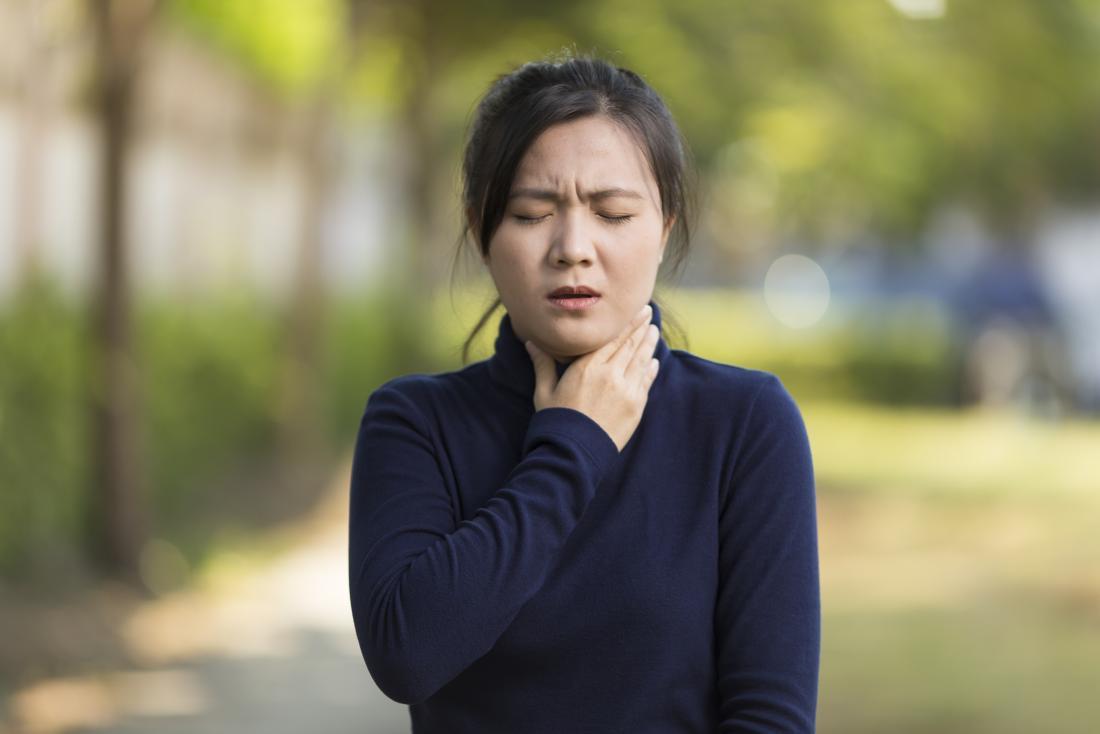 Kobieta cierpiąca na wstrząs anafilaktyczny trzymający gardło z powodu trudności z oddychaniem.