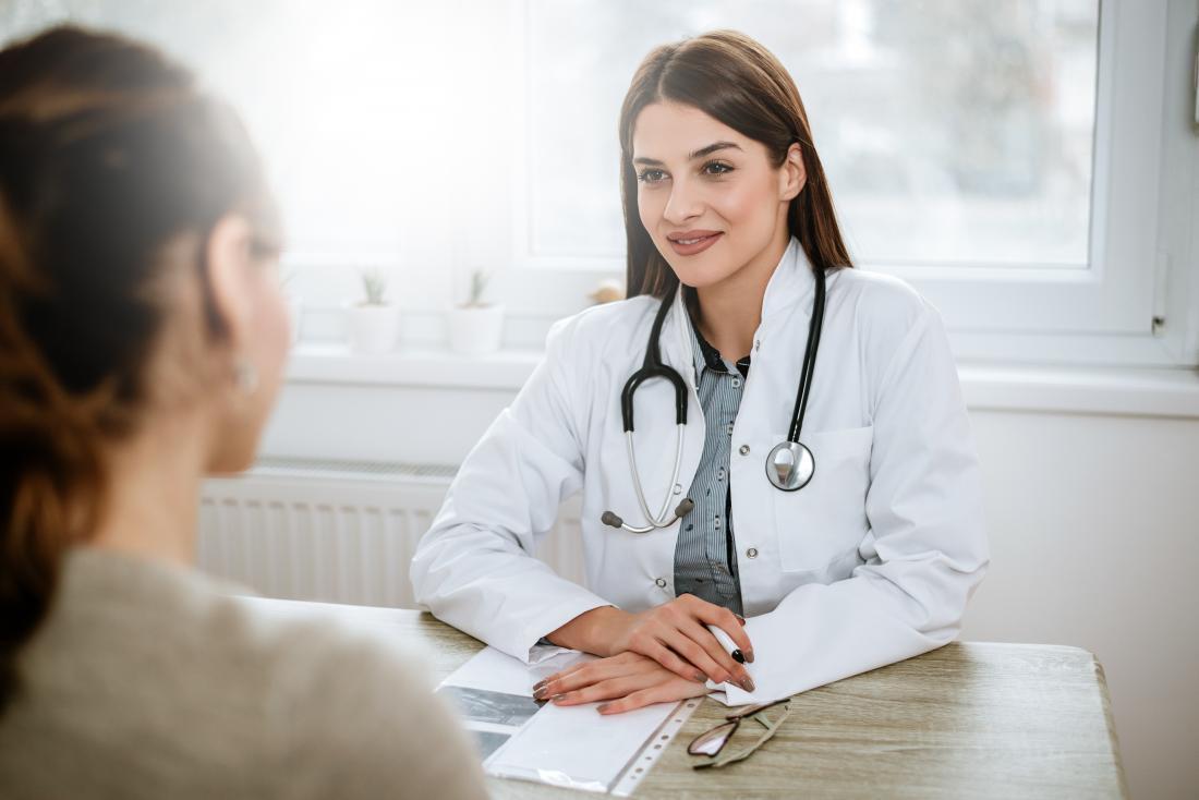 Lekarka przy biurkiem słucha pacjent w przedpolu.