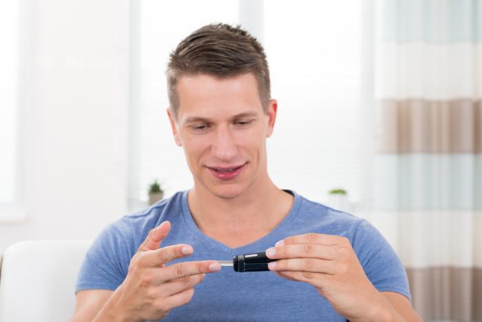 Ein Mann testet seinen Blutzucker mit einem Glucometer.