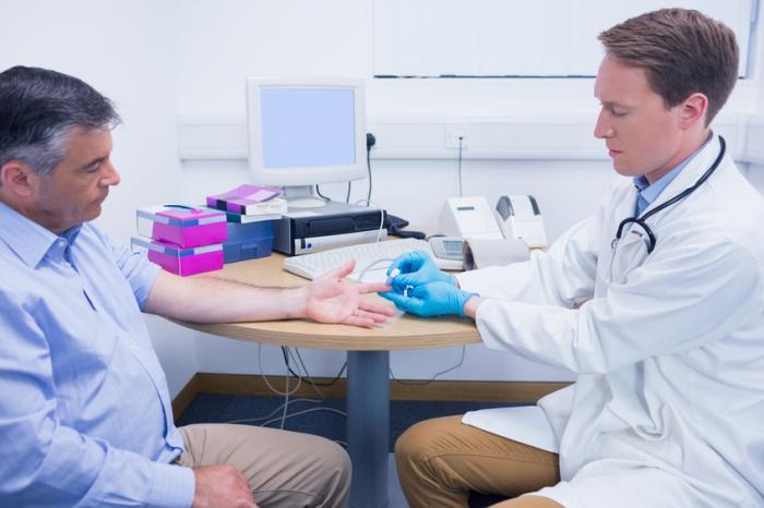 Ein Arzt testet den Blutzuckerspiegel eines Mannes.