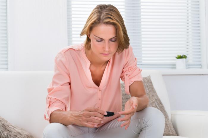 女性がグルコースメーターを見ている。