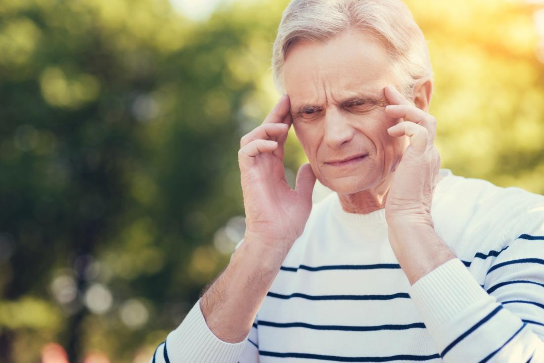 Homem sênior ao ar livre massageando templos por causa de problemas de dor de cabeça, desorientação e visão.