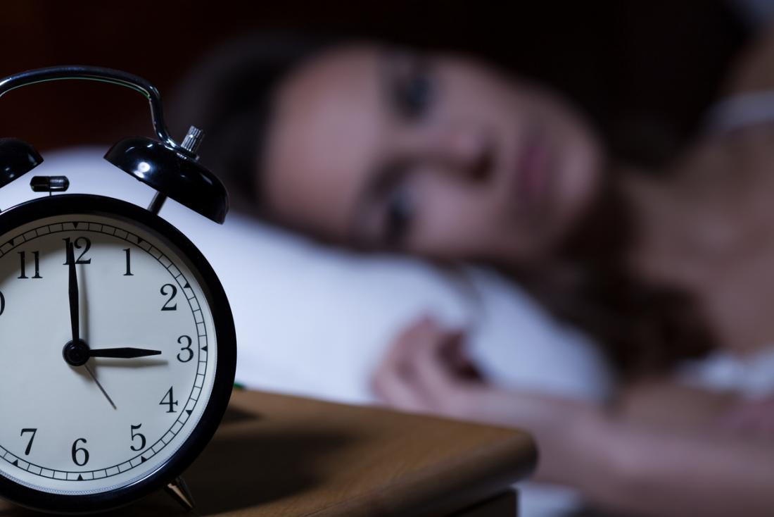 dame avec l'insomnie regardant à l'arrière de son horloge