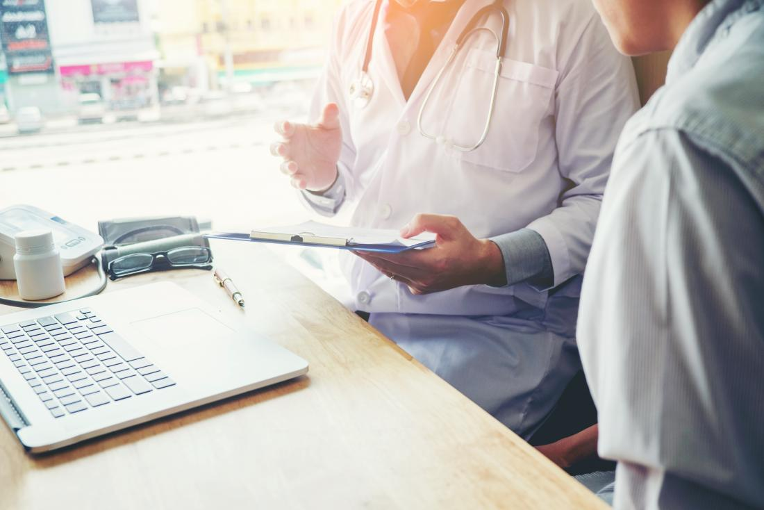 docteur avec presse-papiers dans le bureau discuter avec le patient au premier plan