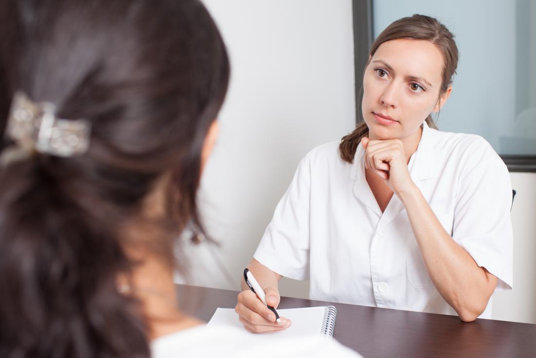 Nữ bác sĩ hoặc bác sĩ phụ khoa lắng nghe thông cảm với bệnh nhân nữ ở tiền cảnh.