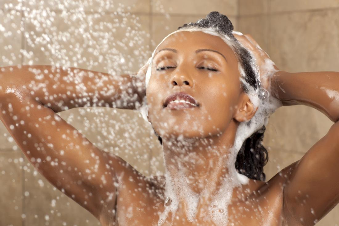 頭皮の湿疹を助けるためにシャワーでシャンプーを使用する女性