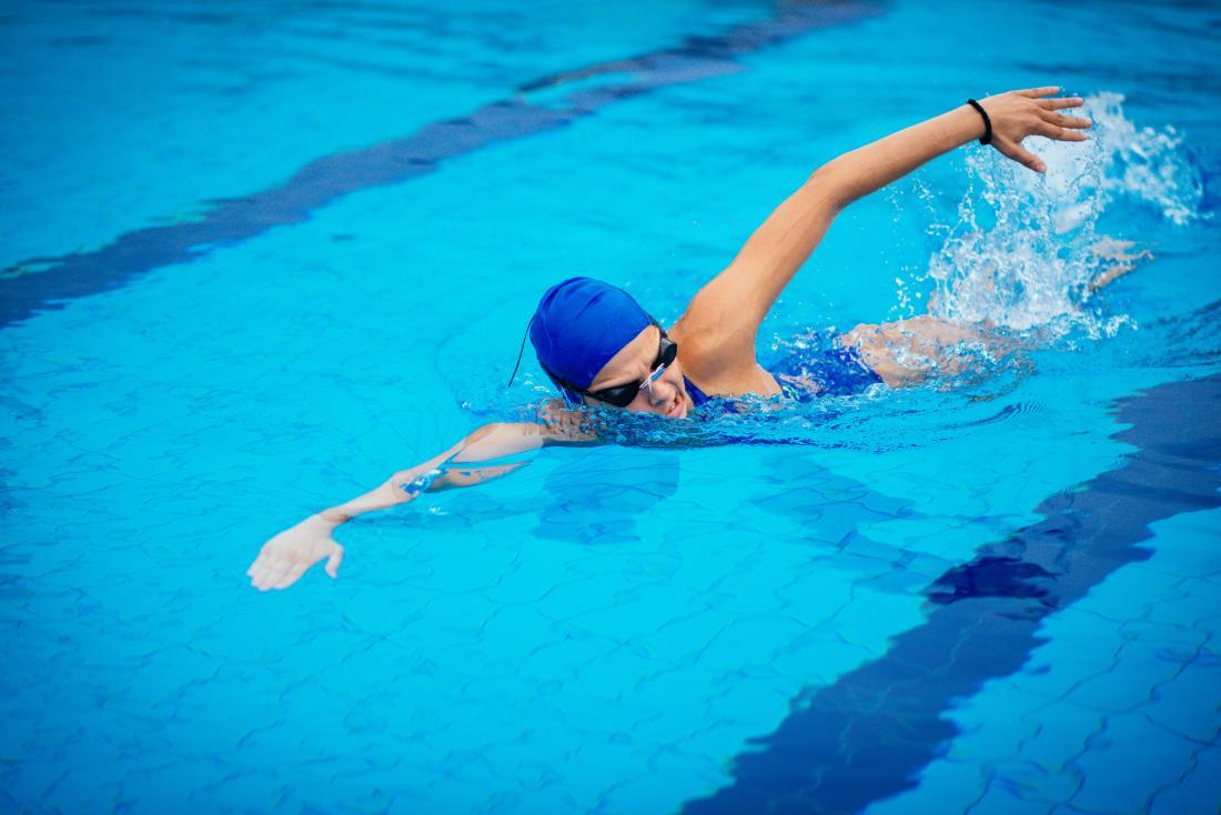 プールで泳ぐ女性。