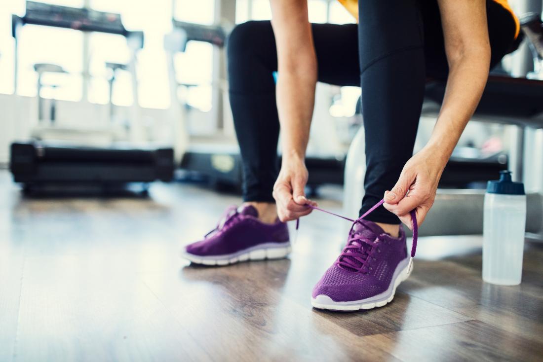 Mulher que amarra mostras running na ginástica.