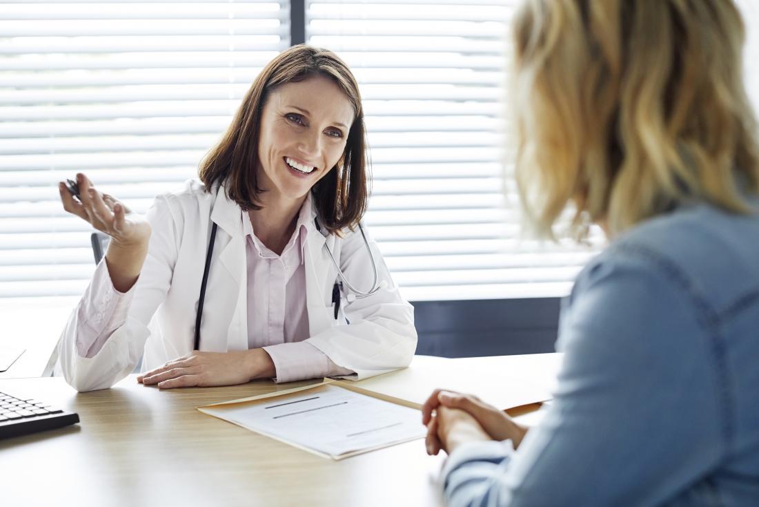 Doutor fêmea atrás da mesa que sorri e que fala ao paciente no primeiro plano.