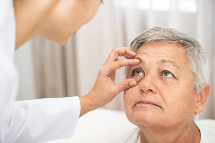 Um médico inspeciona um olho direito de senhoras