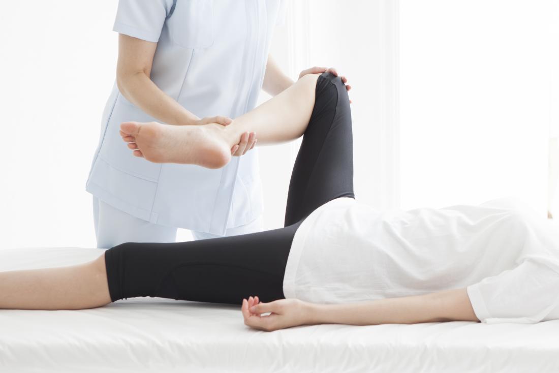 Kobieta o nodze naciągnięta na fizjoterapeutów.