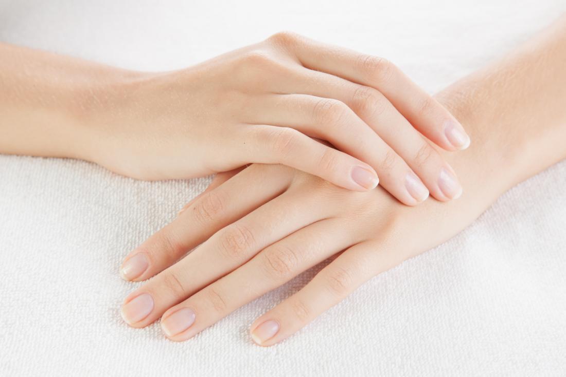 Bàn tay của người phụ nữ với móng tay cắt tỉa cẩn thận gấp trên khăn trắng.
