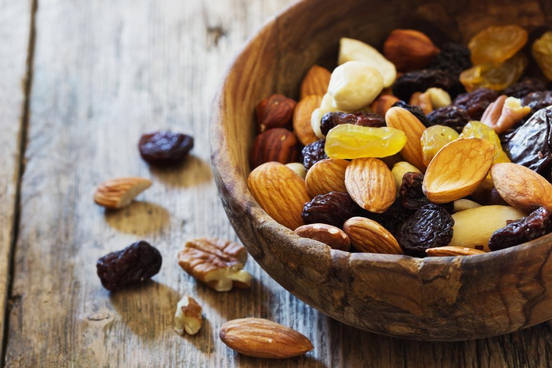 Trái cây sấy khô và các loại hạt trong một bát gỗ, bao gồm nho khô, chuối, hạnh nhân và quả phỉ.