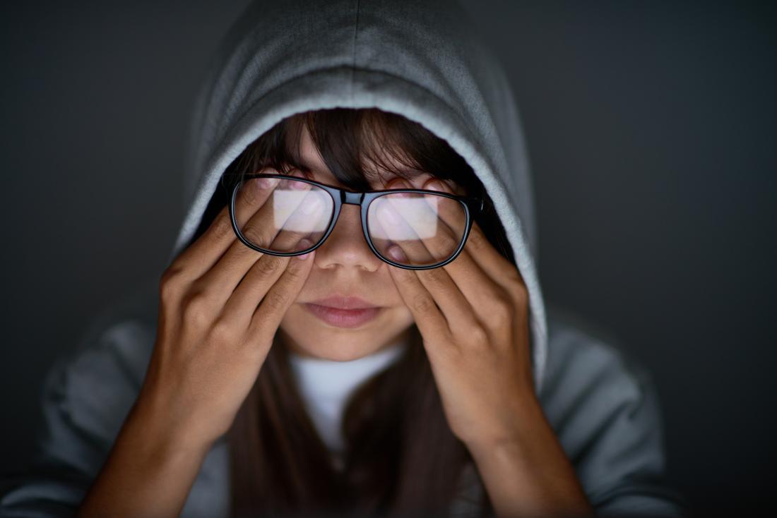 眼鏡の下で目をこすりながら彼女の目の後ろに圧力を持つ女性。