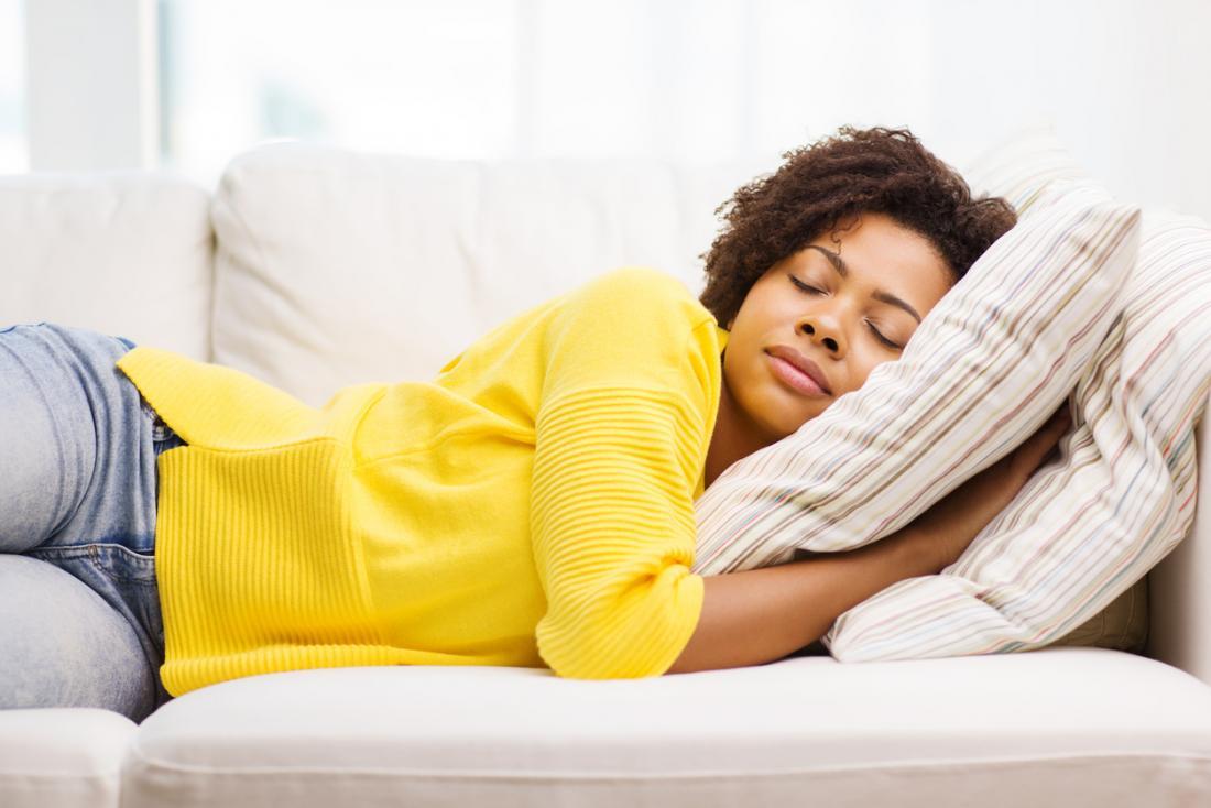[ソファーで寝ている黄色いセーターの女性]