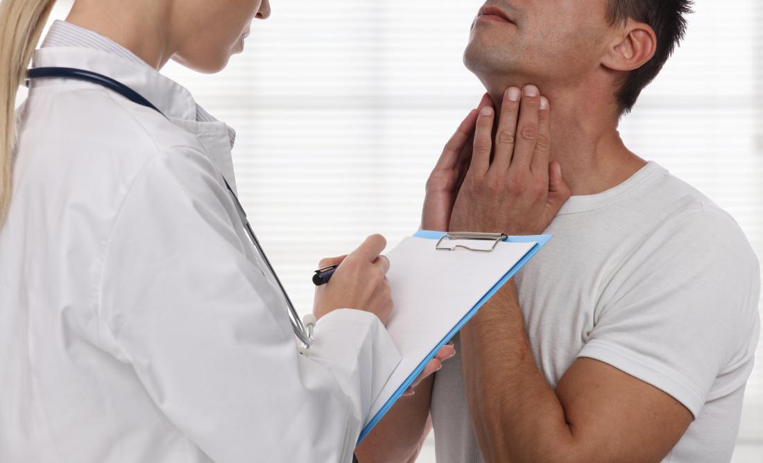 Paciente masculino que explica o problema com garganta e pescoço ao doutor fêmea com prancheta.