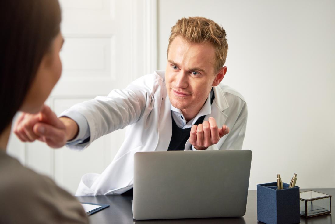 Doktor, der auf Patientenkinn vor Laptop zeigt.