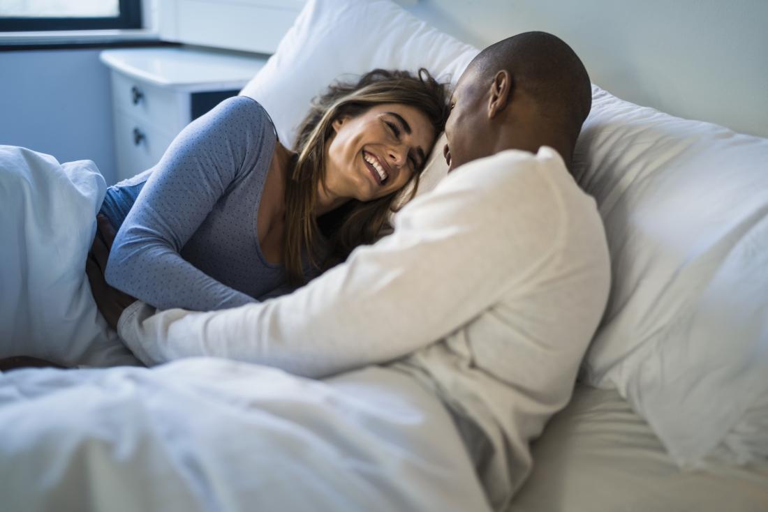 Uomo e donna a letto, ridendo.