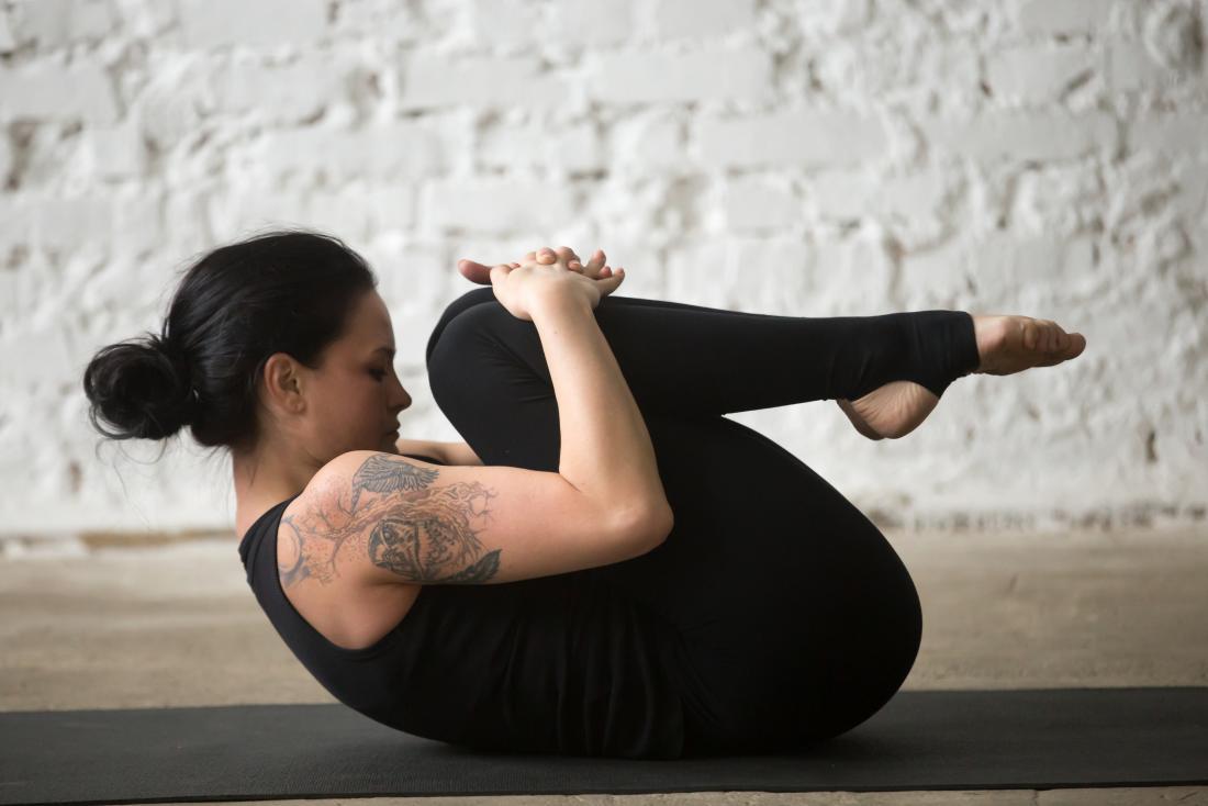 donna che abbraccia le ginocchia al petto in posa yoga.