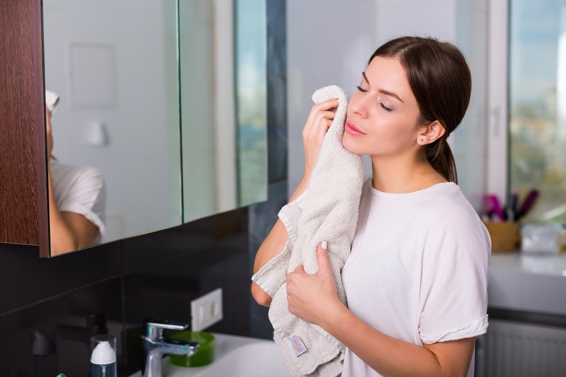 タオルで彼女の顔を乾燥させた女性