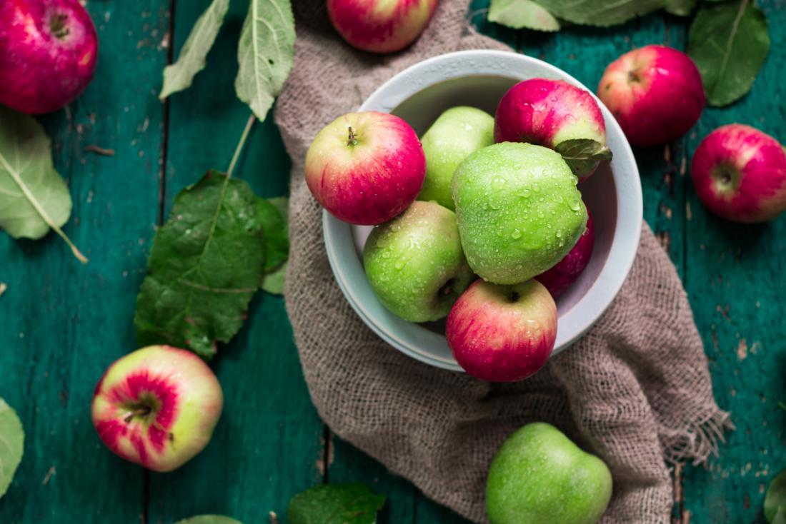 Pommes vertes et rouges dans un bol, et sur une table en bois.