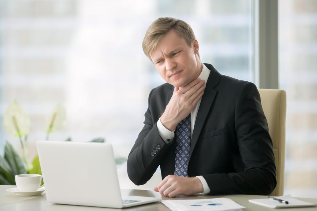 Homme en costume d'affaires au bureau en face de l'ordinateur portable, tenant son mal de gorge dans la douleur.