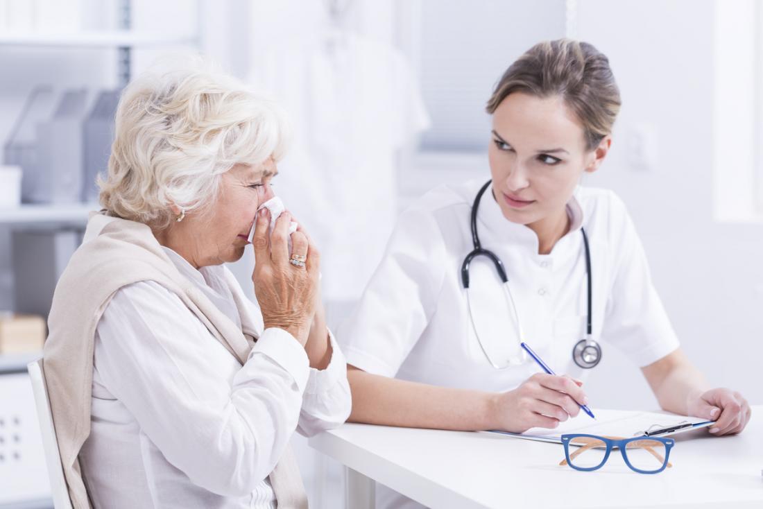Femme âgée se mouchant le nez en parlant à un jeune médecin des allergies et du rhume des foins.