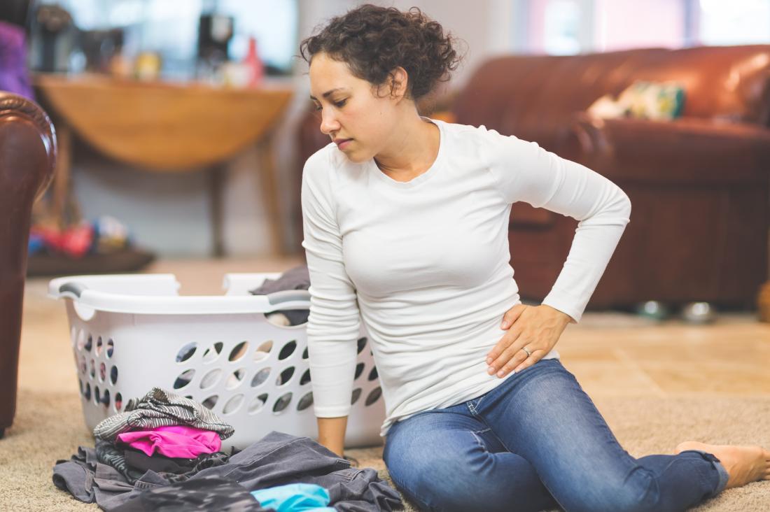 Frau, die auf dem Fußboden mit dem Waschen hält Seite in den Schmerz sitzt