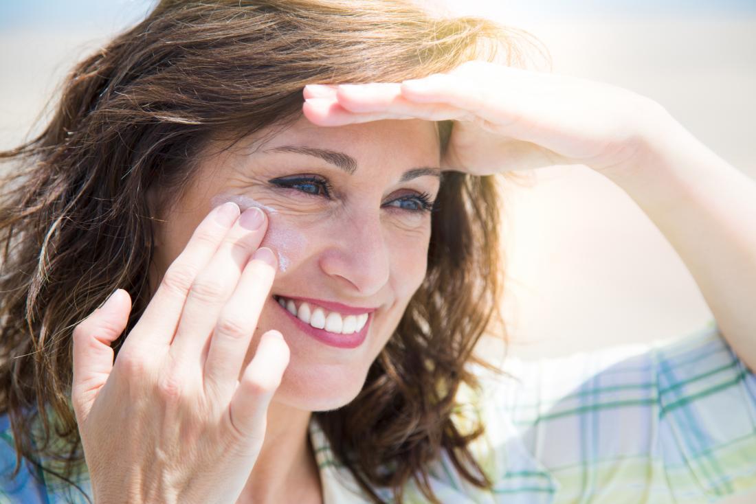 Donna invecchiata centrale che applica protezione solare per affrontare mentre ombreggiatura osserva da sole e da sorridere.