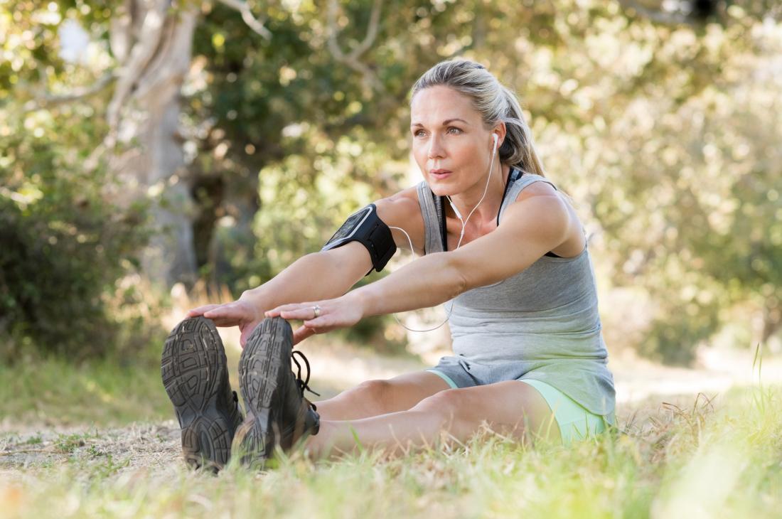 Mulher, sentando, ligado, chão, ao ar livre, dedos tocantes, dedos executando, pé, flexion, bezerro, estiramento