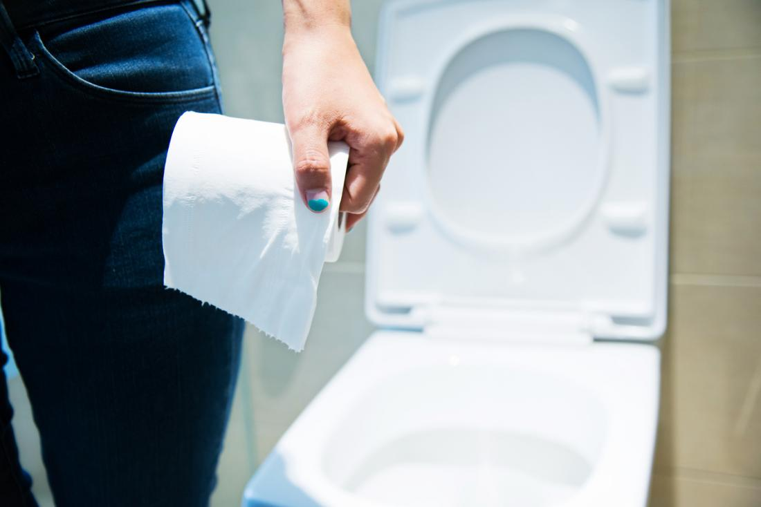 Frau, die vor der Toilette hält Klo Rolle steht.