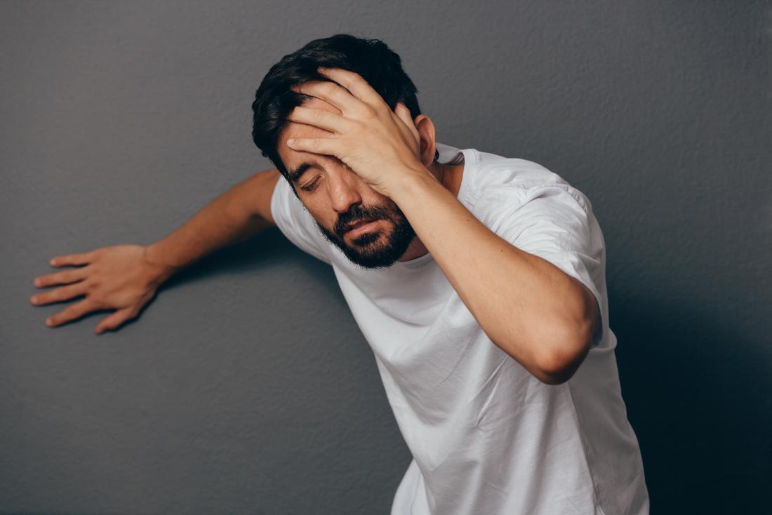 L'homme étourdi en se penchant sur le mur et la tête.