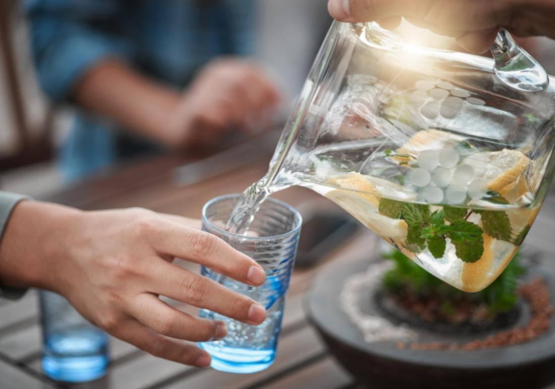 Вода с мента и лимон в кана се изсипва в чаша на натоварена маса.