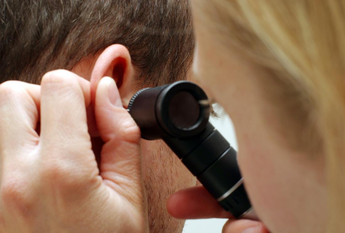 Femme inspectant l'oreille de l'homme.