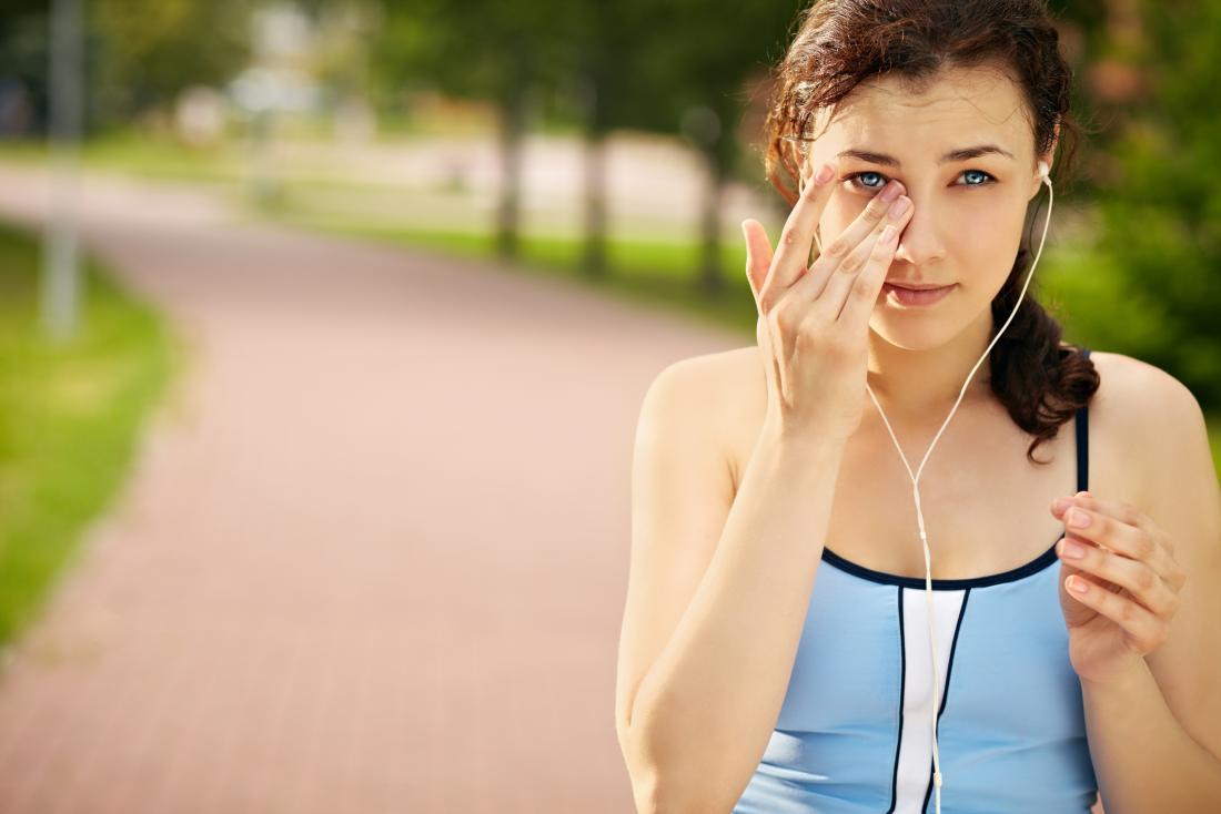 ジョギングの外の女性が目を拭う。