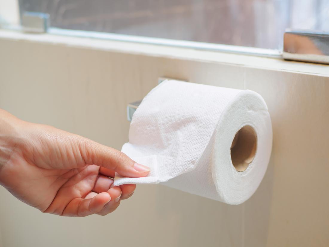 Personne tirant un rouleau de papier toilette qui peut avoir des crottes de mousse
